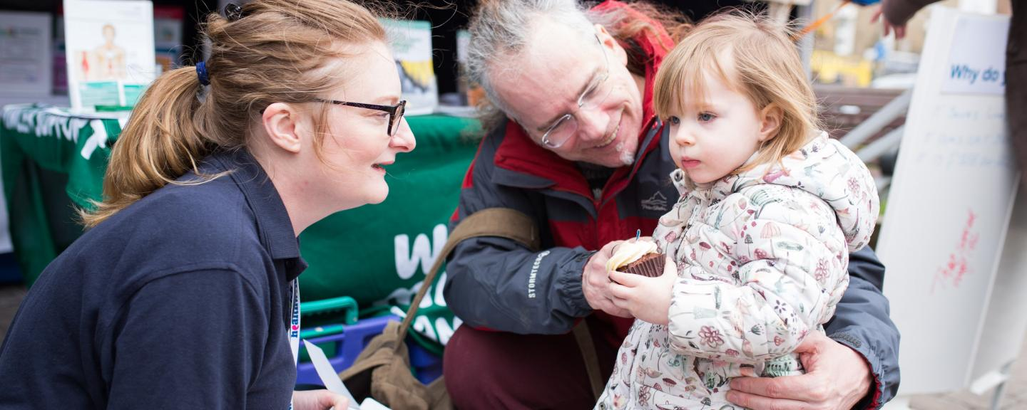 Healthwatch Volunteer talking to a little girl and her dad