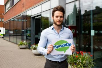 Man holding a sign outside a hospital that says 'Speak Up'