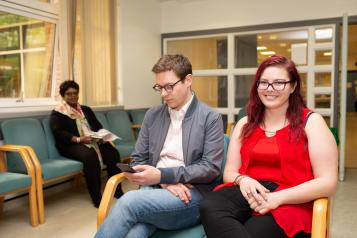 Two people sitting in a waiting room