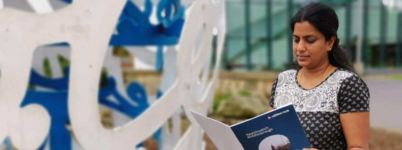 Woman reads Healthwatch leaflet